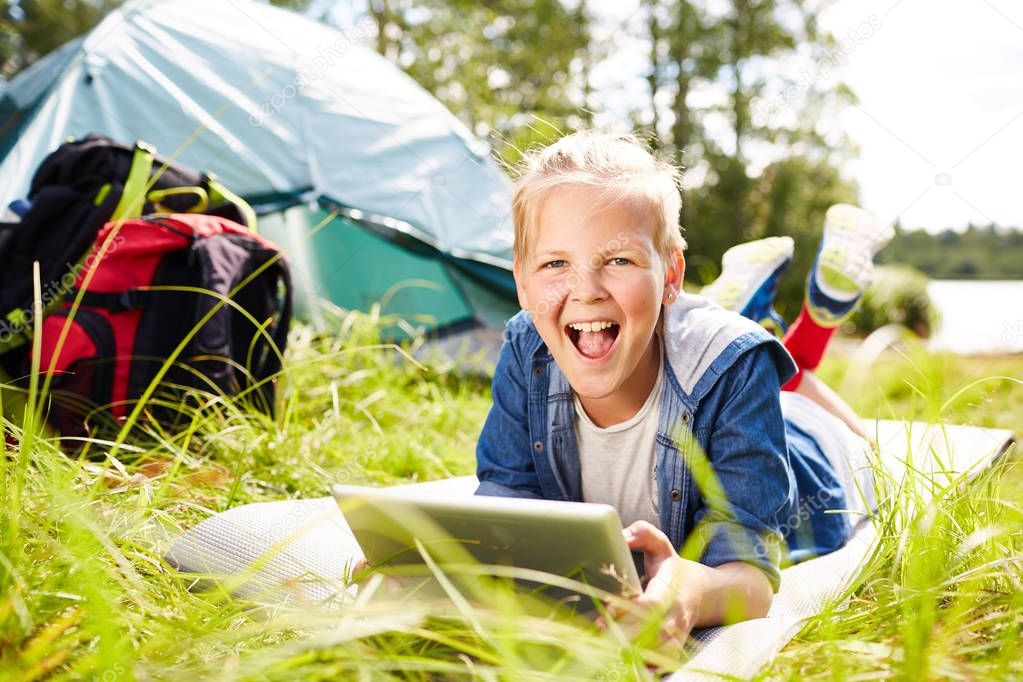 Cheerful boy with tablet relaxing on grass and looking at camera while browsing in the net