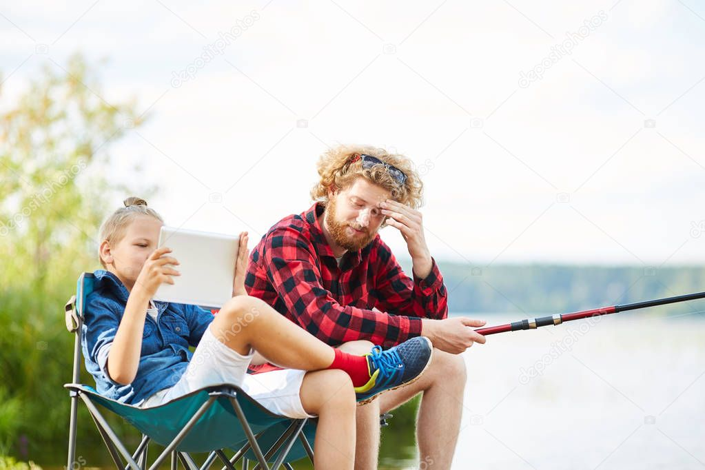 Youthful boy with tablet browsing in the net while sitting next to his father fishing in lake
