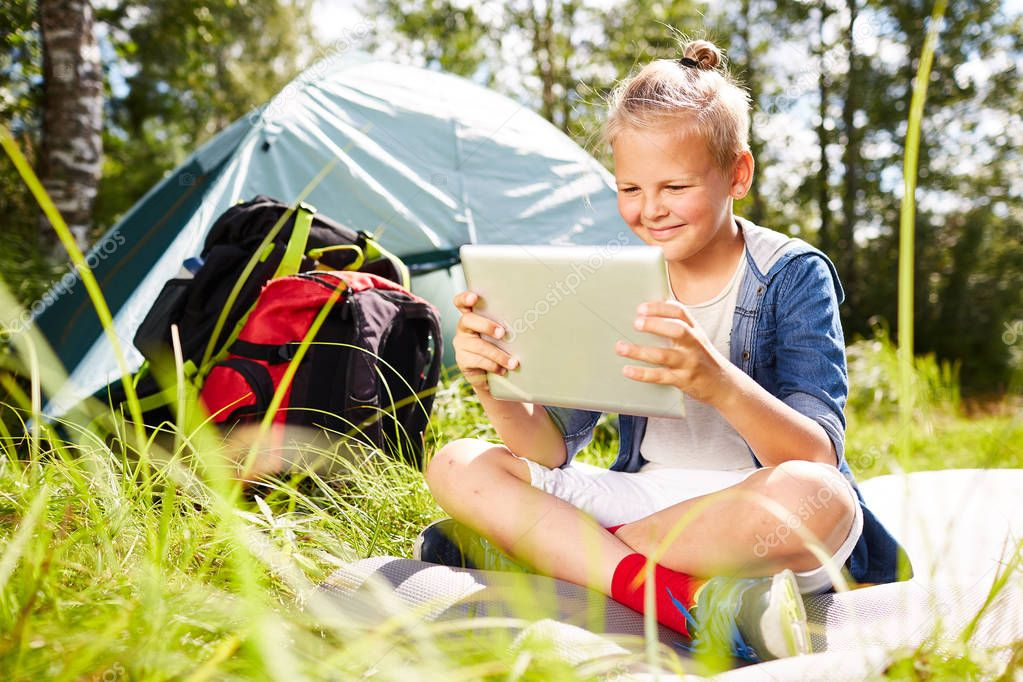 Little backpacker with touchpad sitting on green grass and watching online movie in the afternoon with his tent on background
