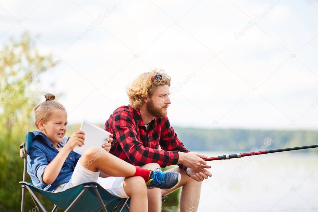 Young restful man fishing by lake with his son sitting near by and watching online video in touchpad