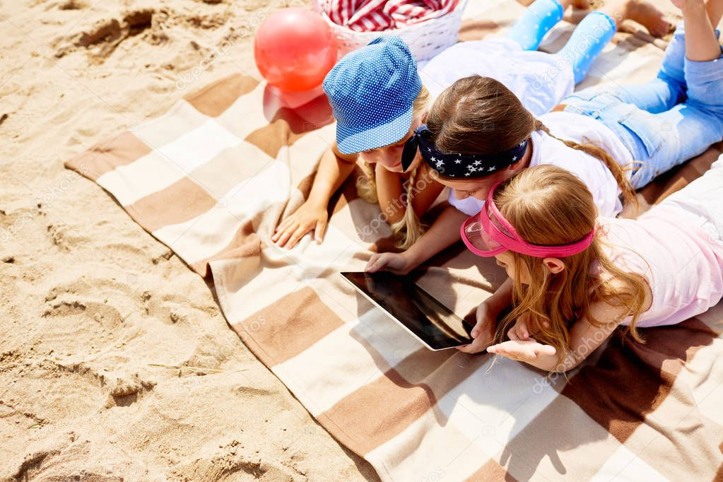 Group of little girls with digital tablet lying on the beach on hot summer day and browsing in the net