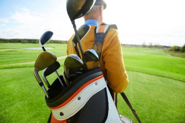 Bunch of golf clubs in bag on shoulder of professional player moving along large green field
