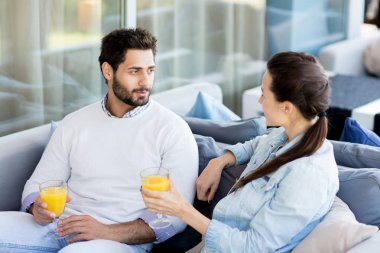 Young amorous man and woman with glasses of juice having rest in cafe and talking
