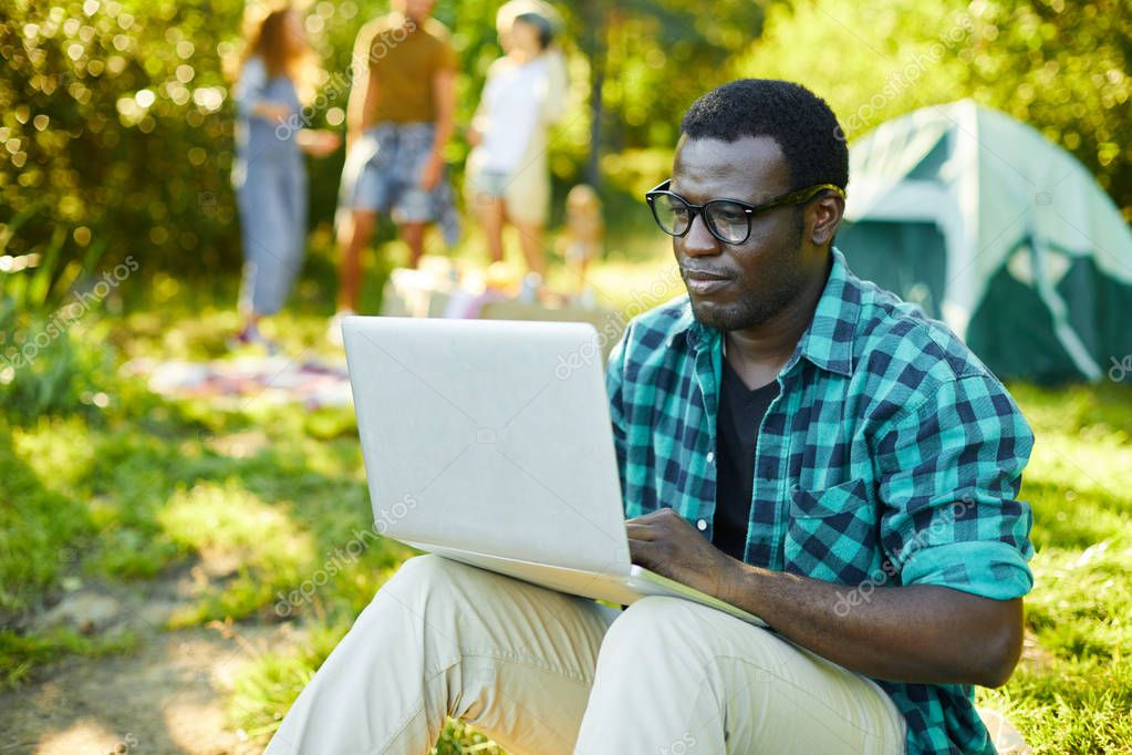 Young businessman in casualwear browsing in the net in natural environment during backpack trip with friends
