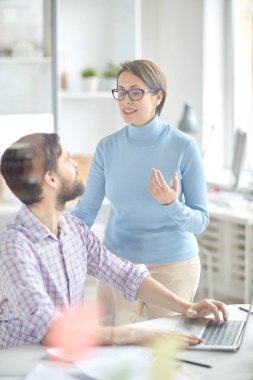 Confident employer standing by workplace of office manager and explaining him the importance of new working instructions