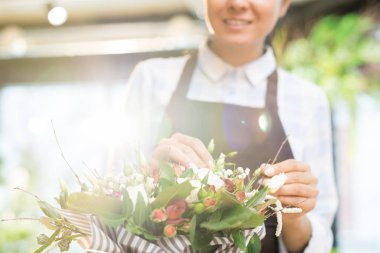 Contemporary young florist choosing fresh flowers before making new bouquet for client