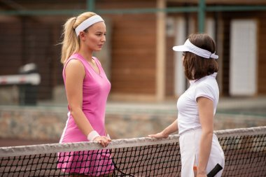 Two girls in activewear standing by net and discussing points of game of tennis