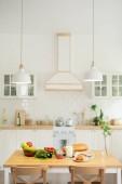 Belső konyha a modern lakás vagy ház konyhai és lámpák lógó asztal zöldség-és házi készítésű ételek