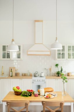 Interior of kitchen in modern flat or house with kitchenware and lamps hanging over table with vegetables and homemade food stock vector