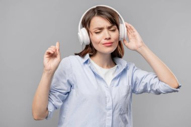 Young brunette female in headphones enjoying her favorite music while posing in isolation