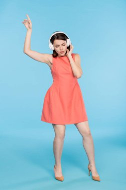 Young elegant woman in red dres enjoying music in headphones while dancing in isolation