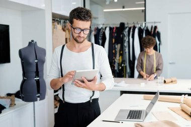 Young serious male tailor with tablet looking through online creative ideas while working over new fashion collection
