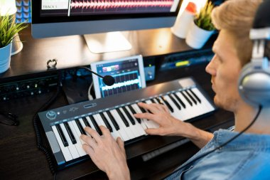 Hands of young man on piano keyboard during work over new music recording in contemporary studio