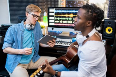 Young singer or musician of African ethnicity playing the guitar and singing while his colleague recording the song in studio