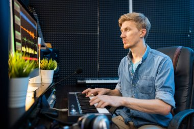 Young casual blonde man looking at computer screen while pressing keys of piano keyboard in sound recording studio