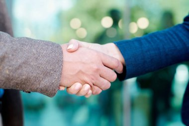 Hands of young contemporary employees in handshake symbolizing partnership, trust and unity