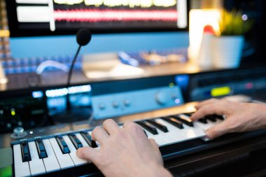 Hands of young musician pressing keys of piano keyboard in front of microphone and computer monitor while recording music