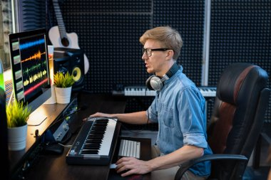 Young male deejay in denim shirt looking at sound mixing tracls on computer screen while sitting by desk in front of monitor stock vector