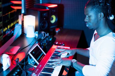 Young serious African-american man making new music while sitting in studio in front of pianoboard and pressing keys