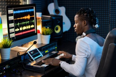 Serious young African man pressing keys of piano keyboard and looking at tablet display with waveforms sound visualization