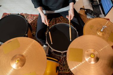 Overview of hands of young drummer or musician with drumsticks having rehearsal at home, in garage or studio at leisure