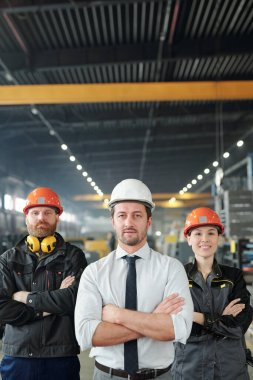 Confident factory team of professionals in hardhats standing with crossed arms in contemporary shop of large plant stock vector