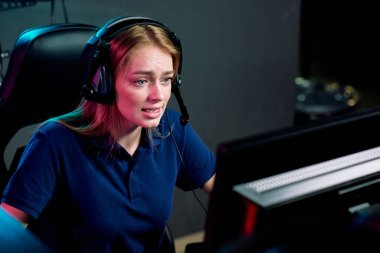 Young female e-sport addict in headset looking at computer screen during cyber competition while sitting in modern game club