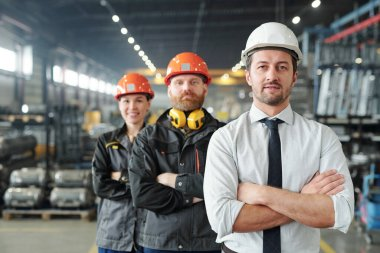 Confident leaders of manufacturing production plant standing with crossed arms in row at factory stock vector