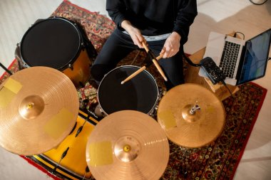 Top view of young male musician in casualwear holding crossed drumsticks over black drum surrounded by cymbals while playing instruments