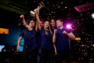 Five ecstatic young friendly video gamers expressing pride of their winning in cybersports competition while standing in falling confetti