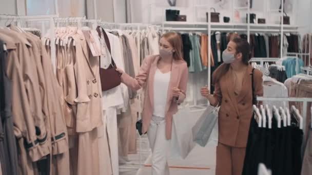 Střední záběr mladých žen přátel v obličejových maskách nakupování společně v obchodě s oblečením