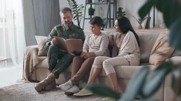 Mittlere Aufnahme eines bärtigen Mannes in Militäruniform, der auf einer Couch sitzt und aus dem Einsatztagebuch seiner liebenden Frau vorliest. Glückliche Frau und Junge hören zu