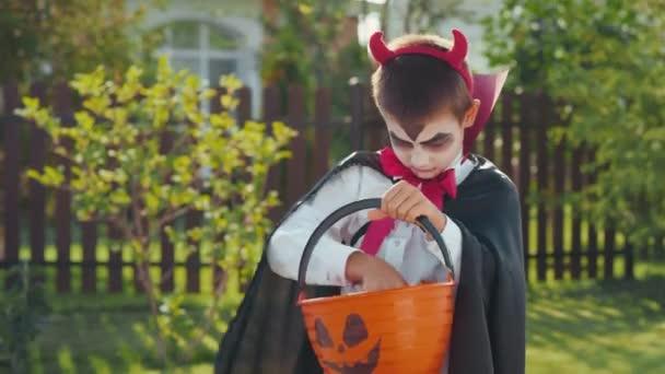 Naklonit portrét záběr roztomilého chlapečka v halloween kostýmu s pláštěm při pohledu do koše a počítání cukroví sbíral koledování v okolí, pak se podíval nahoru a usmíval se na kameru
