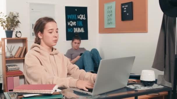 Követés lövés vidám lány ül az asztalnál a kollégiumi kollégiumban, és gépelés laptop, majd kérdéseket tesz fel a szobatársa pihentető ágyban a háttérben