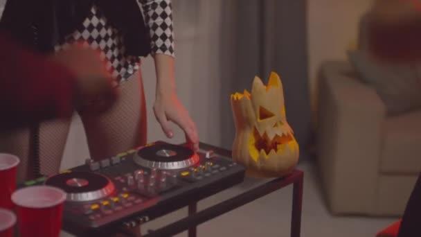 Ruční záběr mladé ženy v kostýmu klauna pomocí DJ regulátoru a hraje hudbu na party na Halloween