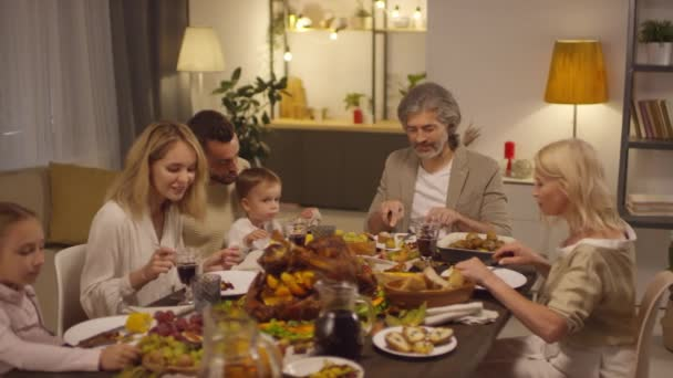 Slow motion shot footage of modern big family gathered together on Thanksgiving day having dinner