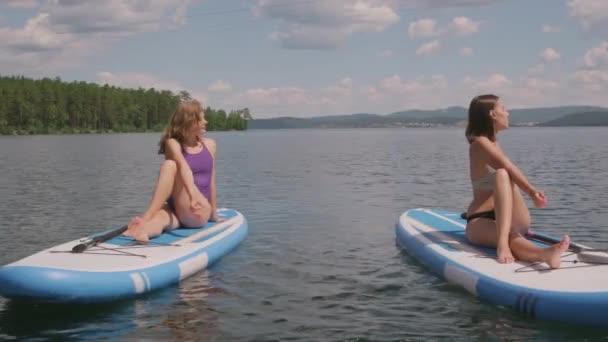Full-shot sportovních dívek v plavkách cvičení a provádění jógy pózuje společně sedí na sup u jezera