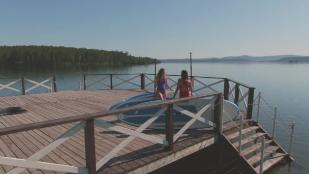 Panning footage of two young women in sports swimwear standing on lake pier chatting holding sup surfing equipment
