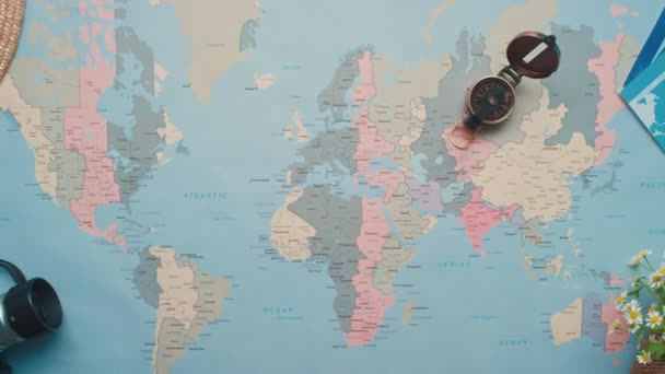 Horizontal zoom out from above flat lay shot of world map with travel objects on wooden table