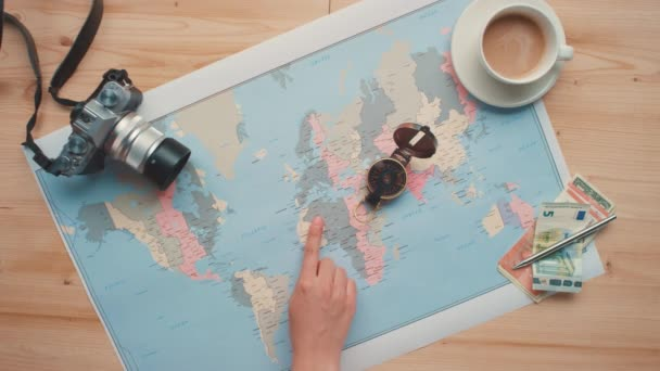 Conceptual horizontal from above flat lay footage of female hands studying world map pointing at places for travelling