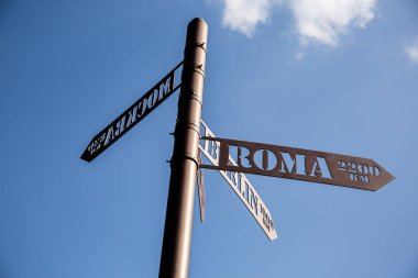 Street sign in retro style indicating directions to different places of the world: Rome, Berlin, Moscow and the information of distance in kilometers. Close-up.