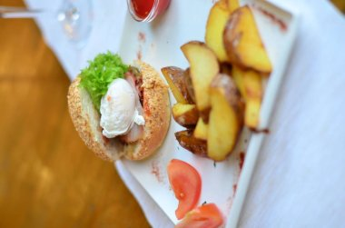 fried potatoes sliced with burger and poached egg with sauce