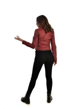 full length portrait of brunette girl wearing red leather jacket, black jeans and boots. standing pose, isolated on white studio background.