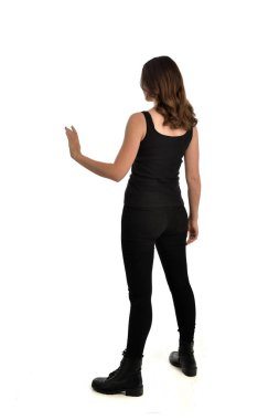 full length portrait of brunette girl wearing black singlet, jeans jeans and boots. standing pose, facing away from the camera. isolated on white studio background.