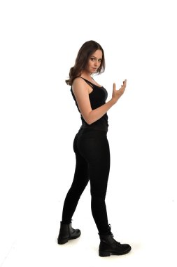 full length portrait of brunette girl wearing black singlet, jeans jeans and boots. standing pose. isolated on white studio background.