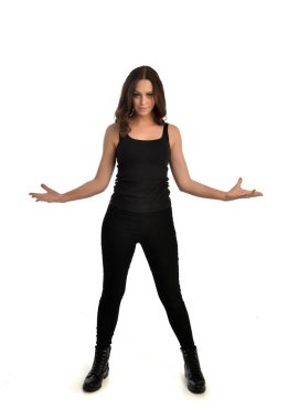 full length portrait of brunette girl wearing black singlet, jeans jeans and boots. standing pose, isolated on white studio background.