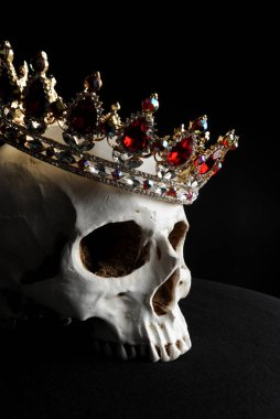 close up of a human skull wearing a red and gold jewelled crown, on black background.