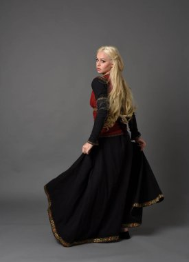 full length portrait of blonde girl wearing red and black medieval costume, standing pose facing away from the camera.