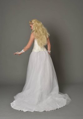 full length portrait of blonde girl wearing white gown, standing pose with back to the camera. grey studio background.