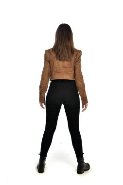 full length portrait of brunette girl wearing leather jacket and plain black clothes. standing pose, isolated on white studio background.